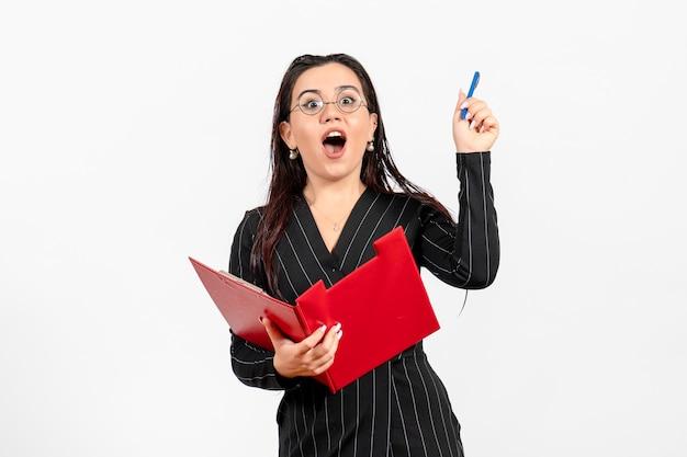 Vue de face jeune femme en costume strict foncé tenant un fichier rouge sur fond blanc travail de document de bureau féminin d'affaires