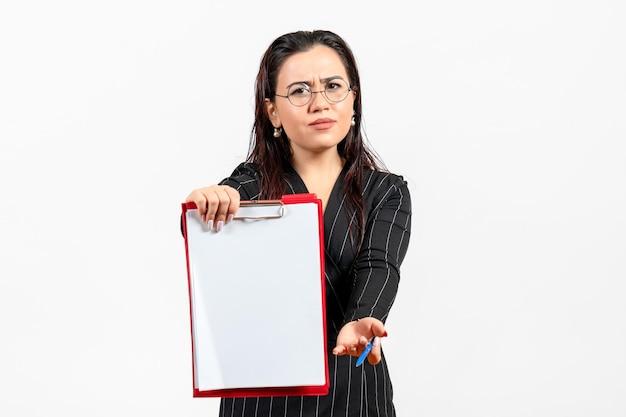 Vue de face jeune femme en costume strict sombre suggérant un fichier rouge sur fond blanc travail de document de bureau féminin d'affaires