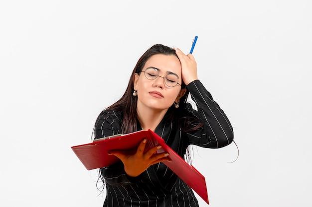 Vue de face jeune femme en costume strict sombre tenant un fichier rouge sur un document féminin de mode d'emploi de bureau de bureau blanc