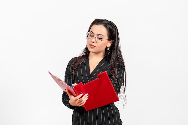 Vue de face jeune femme en costume strict sombre tenant un fichier rouge écrit sur fond blanc bureau d'affaires document féminin travail