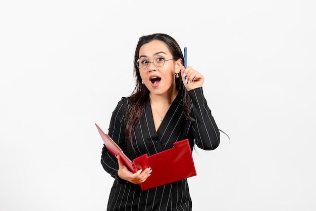 Vue de face jeune femme en costume strict sombre tenant un fichier rouge avec un stylo sur fond blanc bureau d'affaires mode d'emploi document féminin