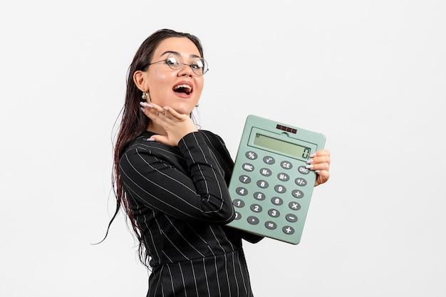 Vue de face jeune femme en costume strict sombre tenant une grosse calculatrice sur fond blanc beauté femme mode entreprise travail de bureau