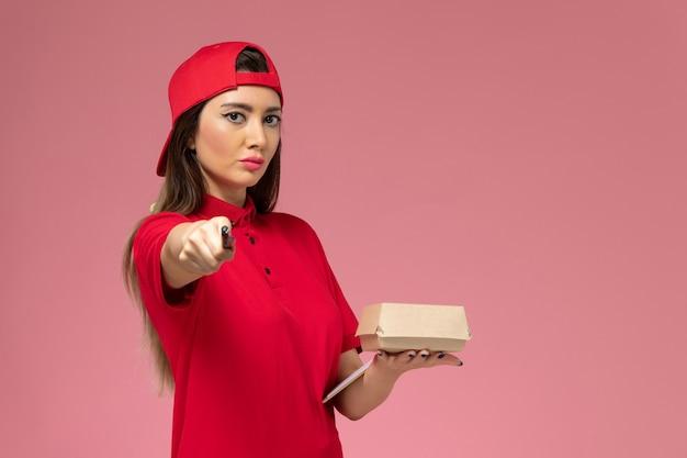Vue de face jeune femme courrier en cape uniforme rouge avec peu de colis de nourriture de livraison et bloc-notes avec stylo sur ses mains sur le mur rose clair