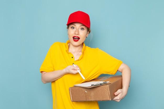 Vue de face jeune femme courrier en chemise jaune et cape rouge tenant le bloc-notes sur le travail de l'espace bleu