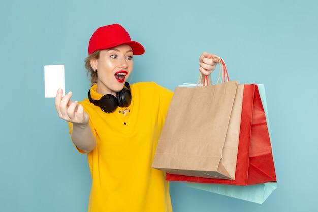 Vue de face jeune femme courrier en chemise jaune et cape rouge tenant multiplier et faire du shopping avec carte sur l'espace bleu