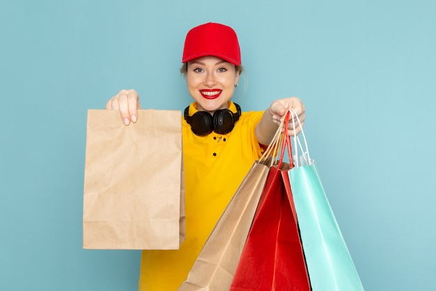 Vue de face jeune femme courrier en chemise jaune et cape rouge tenant multiplier et faire du shopping en souriant sur le travail de l'espace bleu