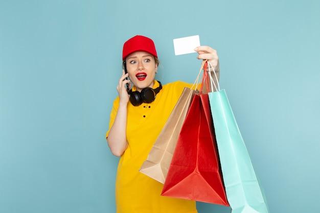Vue de face jeune femme courrier en chemise jaune et cape rouge tenant des paquets d'achat téléphone et carte sur le travail de plancher bleu