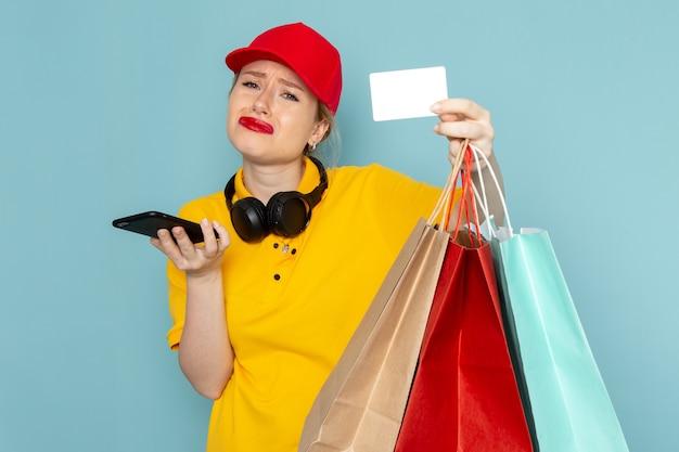 Vue de face jeune femme courrier en chemise jaune et cape rouge tenant des paquets commerciaux téléphone et carte sur l'espace bleu