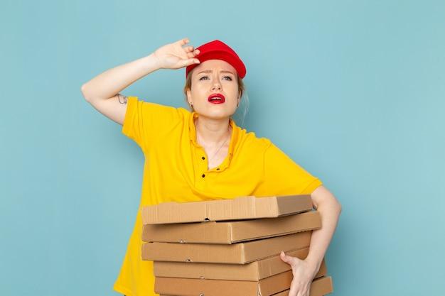 Vue de face jeune femme courrier en chemise jaune et cape rouge tenant des paquets fatigués sur le travail de l'espace bleu