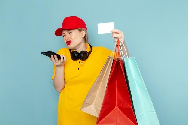 Vue de face jeune femme courrier en chemise jaune et cape rouge tenant des paquets de shopping parler au téléphone sur le travail de plancher bleu