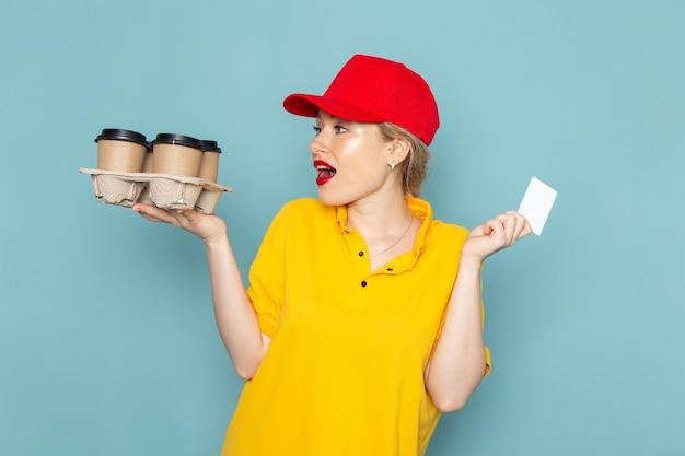 Vue de face jeune femme courrier en chemise jaune et cape rouge tenant des tasses à café en plastique carte blanche sur l'espace bleu femme