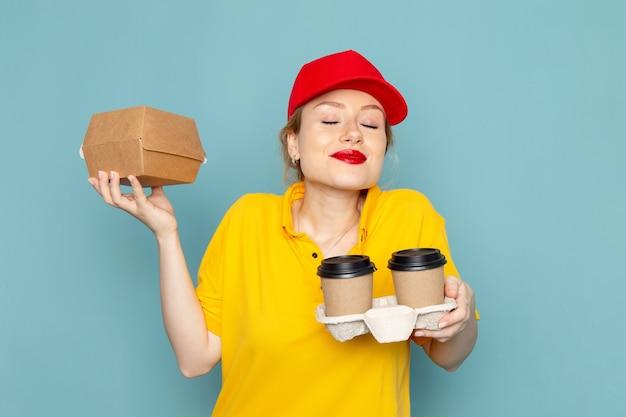 Vue de face jeune femme courrier en chemise jaune et cape rouge tenant des tasses à café en plastique et emballage alimentaire sur l'espace bleu