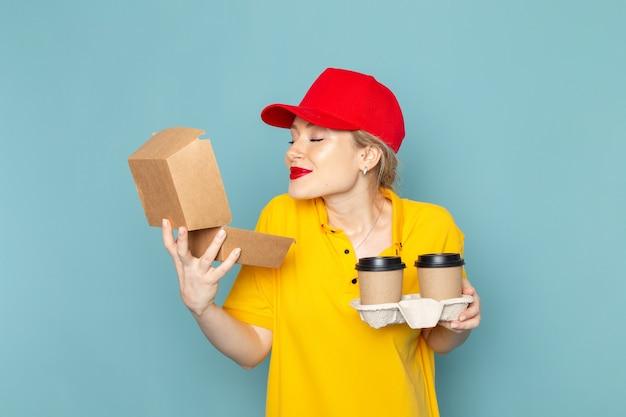 Vue de face jeune femme courrier en chemise jaune et cape rouge tenant des tasses à café en plastique et emballage alimentaire souriant sur le travail de l'espace bleu