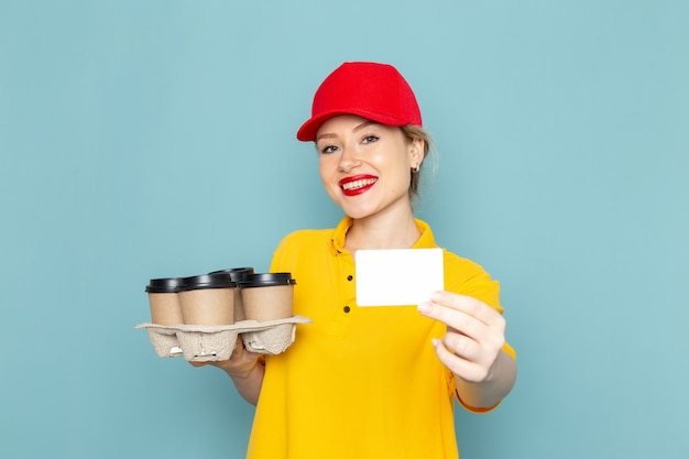 Vue de face jeune femme courrier en chemise jaune et cape rouge tenant des tasses à café en plastique sur le travail de fille femme espace bleu