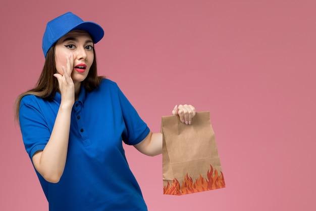 Vue de face jeune femme courrier en uniforme bleu et cape tenant un paquet alimentaire papier chuchotant sur mur rose clair
