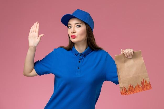Vue de face jeune femme courrier en uniforme bleu et cape tenant un paquet de papier alimentaire sur le modèle de mur rose