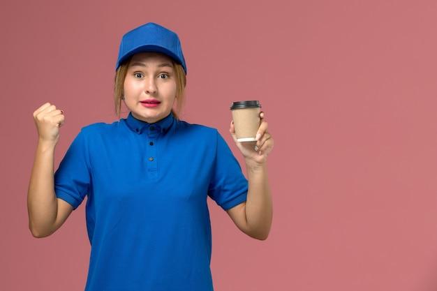 Vue de face jeune femme courrier en uniforme bleu posant tenant une tasse de café de livraison brune, femme de livraison uniforme d'emploi de service