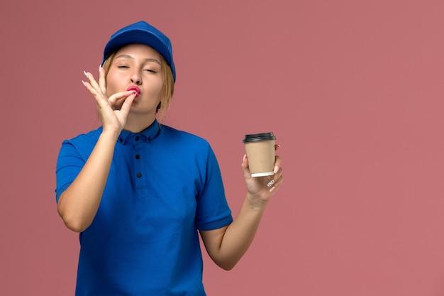 Vue de face jeune femme courrier en uniforme bleu posant tenant une tasse de café de livraison brune sur le mur rose, service de livraison uniforme
