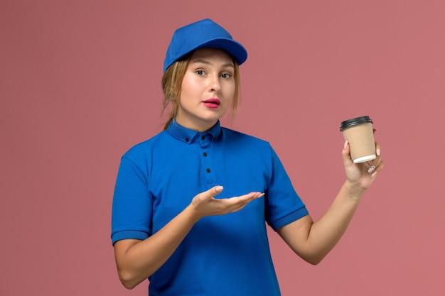 Vue de face jeune femme courrier en uniforme bleu posant tenant une tasse de café de livraison brune, travail de femme de livraison uniforme de service