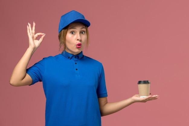 Vue de face jeune femme courrier en uniforme bleu posant tenant une tasse de café de livraison, femme de livraison uniforme de travail de service