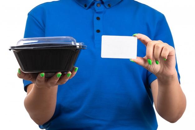 Une vue de face jeune femme courrier en uniforme bleu tenant un bol alimentaire et une carte blanche