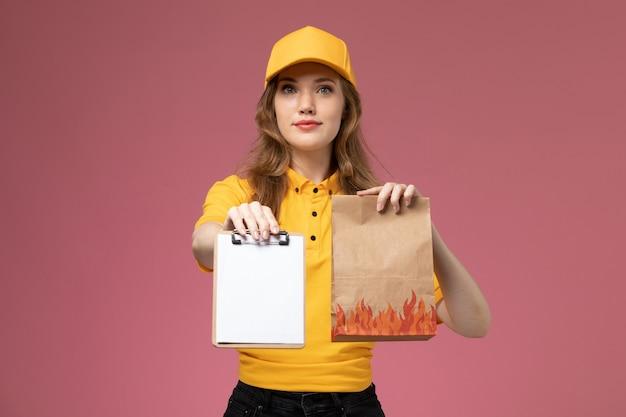 Vue de face jeune femme courrier en uniforme jaune tenant le bloc-notes de colis de nourriture de livraison sur le fond rose service de livraison uniforme