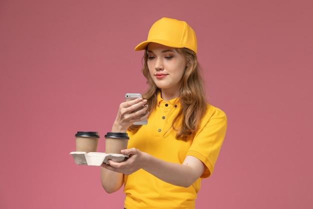 Vue de face jeune femme courrier en uniforme jaune tenant le café de livraison et à l'aide de son téléphone sur le bureau rose travailleur de service de livraison uniforme