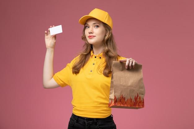 Vue de face jeune femme courrier en uniforme jaune tenant la livraison de colis alimentaires carte blanche sur le service de livraison uniforme de travail fond rose