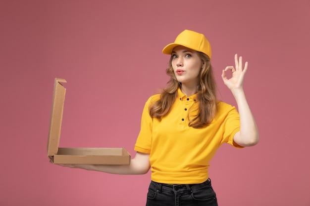 Vue de face jeune femme courrier en uniforme jaune tenant et posant avec boîte de nourriture ouverte sur le travail de bureau rose travailleur de service de livraison uniforme