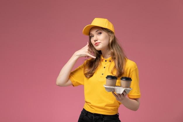 Vue de face jeune femme courrier en uniforme jaune tenant des tasses à café avec une expression mignonne sur bureau rose foncé travail de livraison uniforme travailleur de service