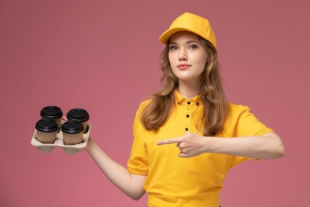 Vue de face jeune femme courrier en uniforme jaune tenant des tasses à café en plastique sur le fond rose foncé travail de livraison uniforme travailleur de service
