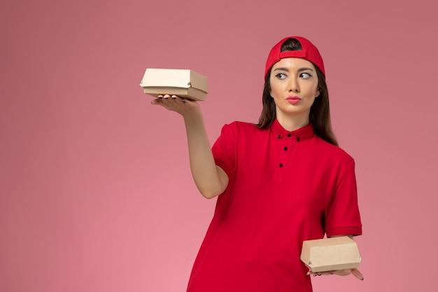 Vue de face jeune femme courrier en uniforme rouge et cape avec peu de colis alimentaires de livraison sur ses mains sur le mur rose