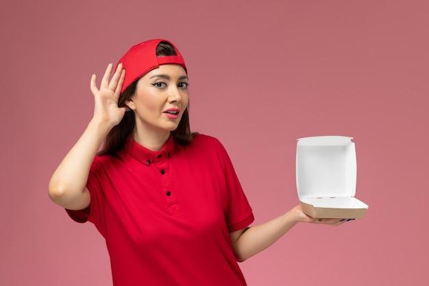 Vue de face jeune femme courrier en uniforme rouge et cape avec peu de colis de livraison de nourriture sur ses mains essayant d'entendre sur le mur rose clair