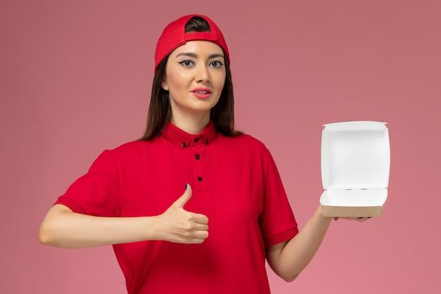 Vue de face jeune femme courrier en uniforme rouge et cape avec peu de colis de livraison de nourriture sur ses mains sur un mur rose clair