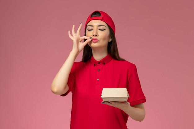 Vue de face jeune femme courrier en uniforme rouge et cape avec peu de colis de livraison de nourriture sur ses mains sur le mur rose