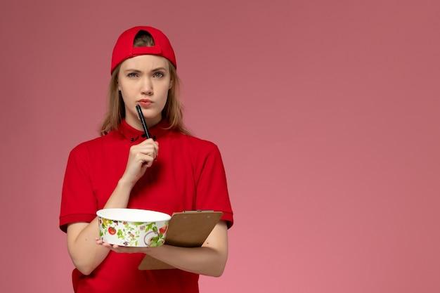 Vue de face jeune femme courrier en uniforme rouge et cape tenant le bol de livraison et le bloc-notes d'écrire des notes et de penser à la livraison uniforme de service de bureau rose