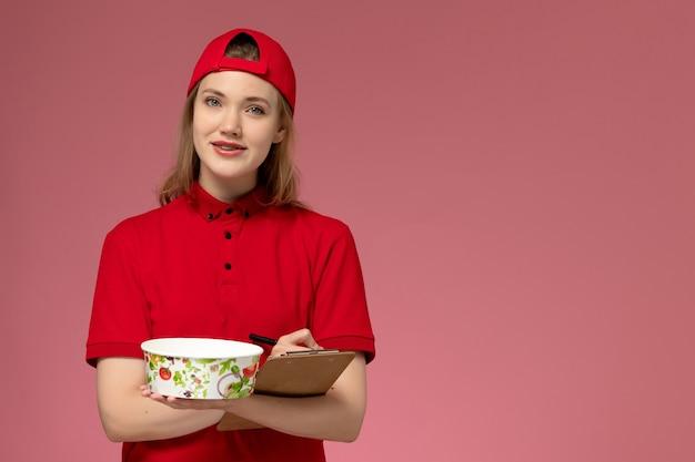 Vue de face jeune femme courrier en uniforme rouge et cape tenant le bol de livraison et le bloc-notes écrivant des notes sur la livraison uniforme de service de travailleur de bureau rose