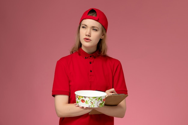 Vue de face jeune femme courrier en uniforme rouge et cape tenant le bol de livraison et le bloc-notes écrivant des notes sur le mur rose