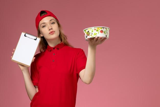 Vue de face jeune femme courrier en uniforme rouge et cape tenant le bol de livraison et le bloc-notes sur mur rose clair