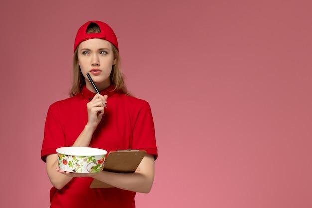 Vue de face jeune femme courrier en uniforme rouge et cape tenant le bol de livraison et le bloc-notes des notes d'écriture sur le mur rose