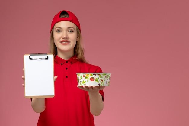Vue de face jeune femme courrier en uniforme rouge et cape tenant le bol de livraison et le bloc-notes avec sourire sur mur rose