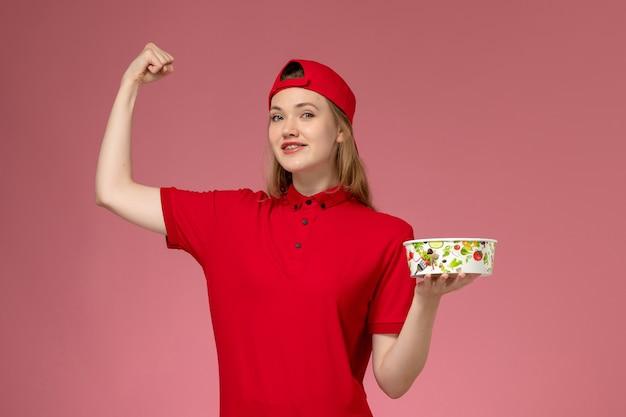 Vue de face jeune femme courrier en uniforme rouge et cape tenant le bol de livraison fléchissant sur le mur rose clair