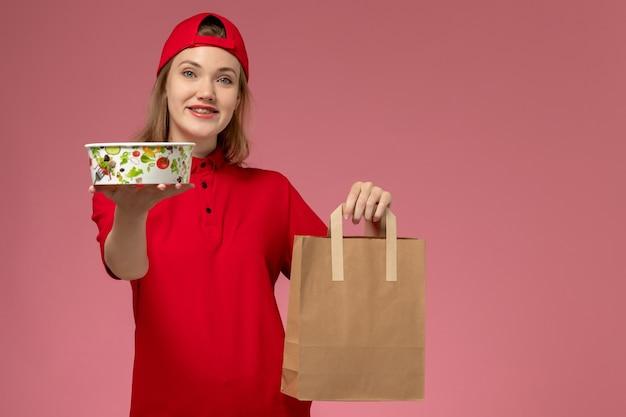 Vue de face jeune femme courrier en uniforme rouge et cape tenant le paquet de nourriture de livraison et bol souriant sur mur rose