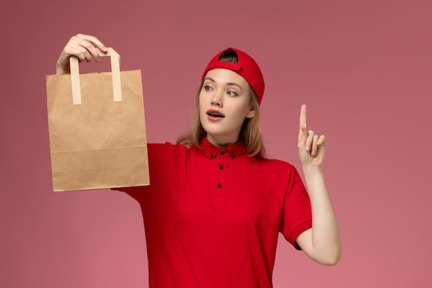 Vue de face jeune femme courrier en uniforme rouge et cape tenant le paquet de nourriture de livraison sur le mur rose
