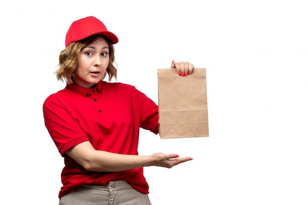 Une vue de face jeune femme courrier en uniforme tenant le paquet de livraison de nourriture