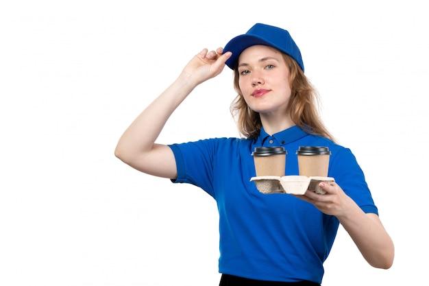Une vue de face jeune femme courrier en uniforme tenant des tasses de café souriant