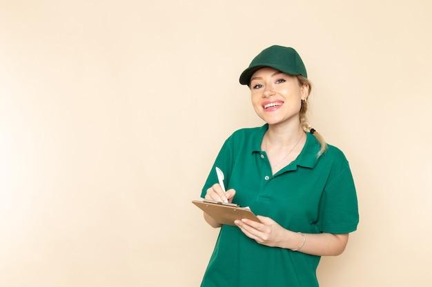 Vue de face jeune femme courrier en uniforme vert et cape verte écrivant des notes souriant sur le travail uniforme femme espace lumière