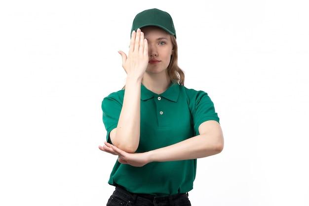 Une vue de face jeune femme courrier en uniforme vert souriant couvrant son un œil avec la main levée