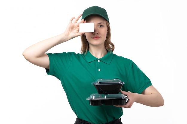 Une vue de face jeune femme courrier en uniforme vert tenant des bols avec de la nourriture carte blanche et souriant sur blanc