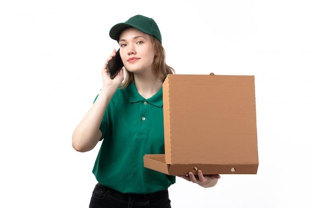 Une vue de face jeune femme courrier en uniforme vert tenant le colis de livraison de nourriture et parler au téléphone